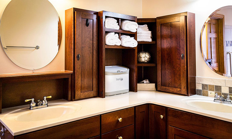 bathroom with custom cherry cabinets and circular mirrors